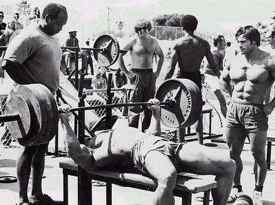 A rúdon három pár 45 fontos és egy-egy húszas. Körülbelül 162 kg. Arnold száznyolcvannal is képesnek bizonyult tíz ismétlésre. A képen csípőre tett kézzel felügyelik